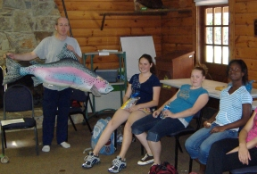 Jeff holding a large fish pillow to describe important identifying characteristics of fish.